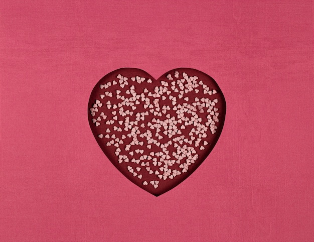 Абстрактный фон с символом любви. сердце вырезать из бумаги на красном фоне, вырезать из бумаги в стиле арт. поделки из бумаги на день святого валентина