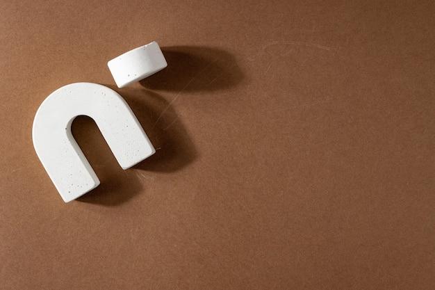 白い幾何学的な形と表彰台と抽象的な背景。コピースペース、ハードシャドウと茶色の背景の円とアーチ