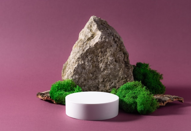 Abstract background with white podium, natural stone and moss