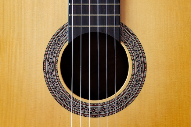 Abstract background wooden spanish classic guitar hole with nylon string on