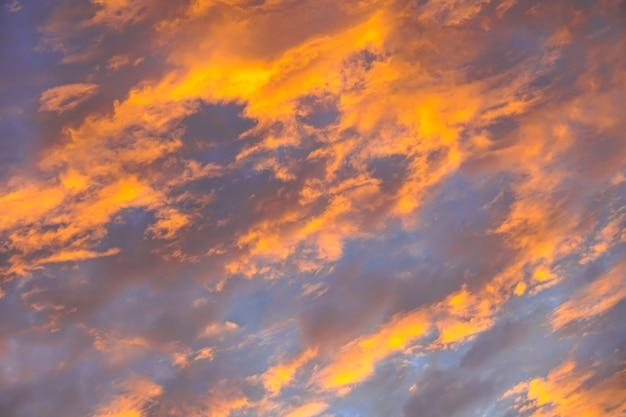 日の出の空に抽象的な美しいオレンジ色のふわふわの雲-カラフルな自然の空のテクスチャの背景