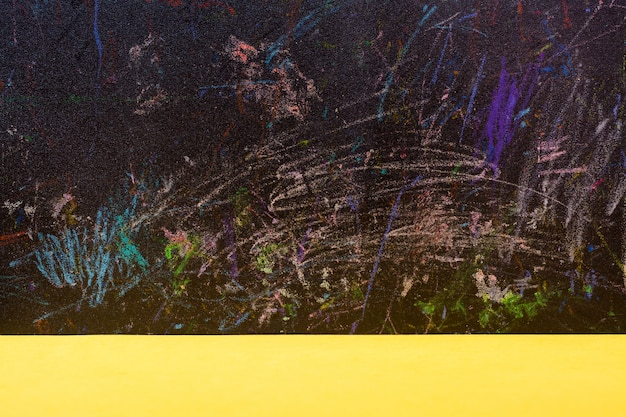 Abstract   black board painted with colored pencils and yellow table