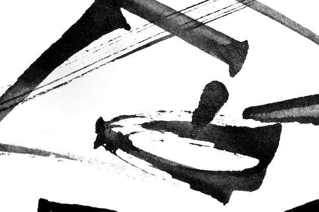Abstract black calligraphy brush strokes and splashes of paint paper on a white background.