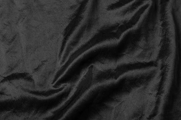 抽象的な黒い布の布テクスチャ背景または液体波または波状のひだ