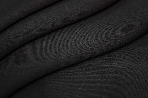 液体の波または波状の折り目が付いた抽象的な黒い布のテクスチャ。