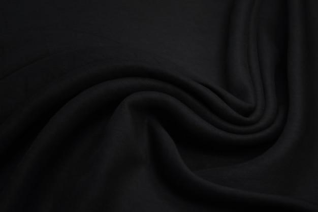 液体の波または波状の折り目が付いた抽象的な黒いリネン生地の布のテクスチャ。