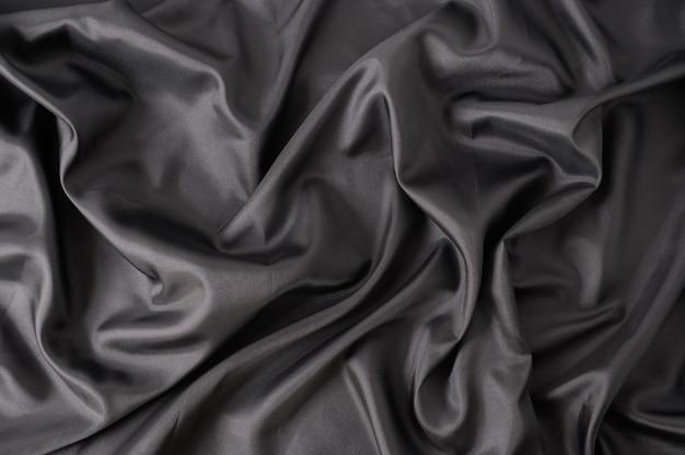 抽象的な黒のサテンの絹のような布。折り目が波状の折り目が付いた生地のテキスタイルドレープ。柔らかな波と、風になびかせてしわくちゃの紙のテクスチャ。