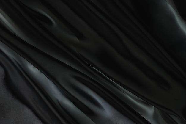 배경을 위한 추상 검정 새틴 실크 천, 주름이 있는 패브릭 텍스타일 드레이프. 부드러운 파도가 바람에 흔들립니다.