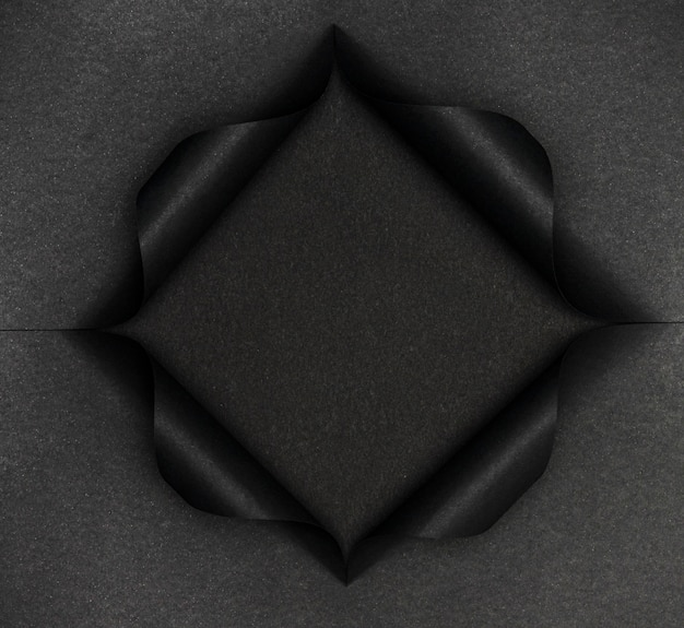 引き裂かれた黒い紙に抽象的な黒い形
