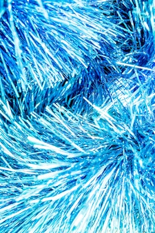 Abstract blue bokeh defocused background.new year background photo with glowing blue tinsel. close-up of shiny metallic texture of holiday decoration.glitter sparkling abstract blue bokeh defocused