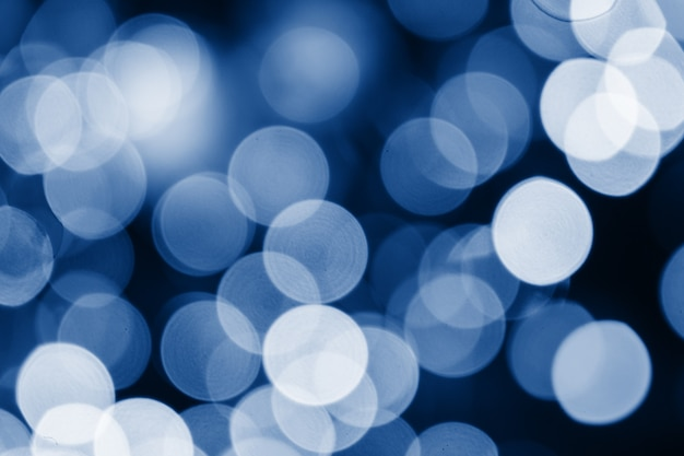 Abstract blue circles bokeh for christmas of any background, defocused. soft colorful blurred and glowing lights toned trendy classic blue color of year 2020