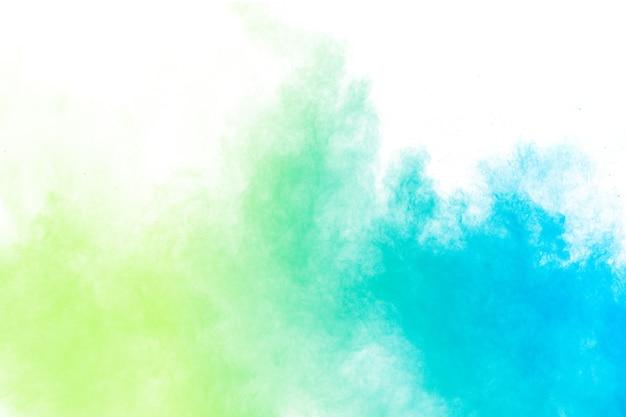 白い背景の上の抽象的な青緑色の粉塵爆発。青緑色の粉塵雲の動きを凍結します。