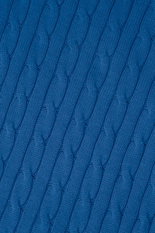 Abstract blue knitwear pattern, background. yarn textured, woven fabric. ornament of braids of sweater. cloth wallpaper.