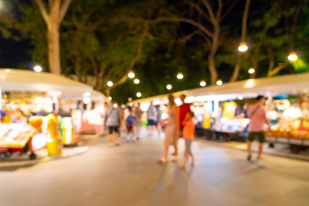 背景の抽象的なぼかしと焦点がぼけた夜のストリートマーケット