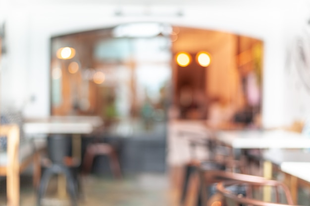 Abstract the blur of the coffee cafe decorated in warm colors makes it look warm. the shop furniture uses brown iron chairs. the tabletop uses white marble, background and cafe concept.