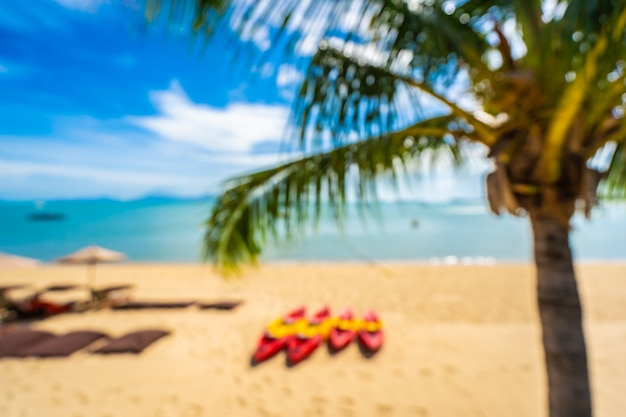 Abstract blur and defocus beautiful tropical beach sea and ocean with coconut palm tree  and umbrella and chair on blue sky