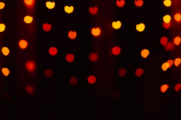 Abstract blur defocused background black, red-orange-yellow lights highlights, bokeh hearts, soft focus