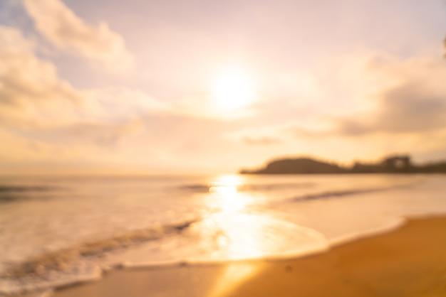 日の出または日没時に抽象的なぼやけた空のビーチの海