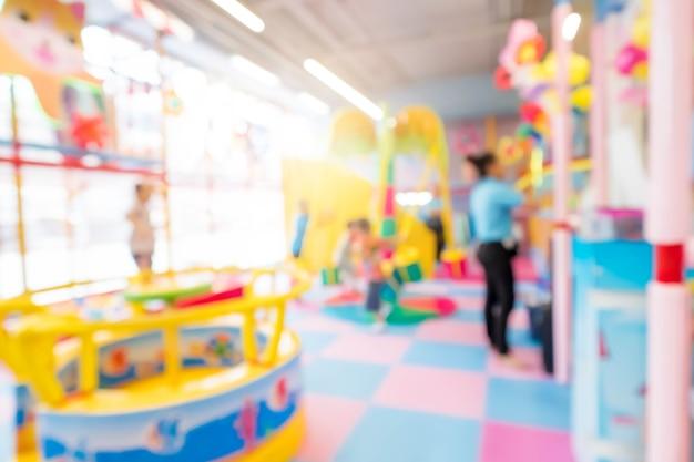 Abstract blur happy kids playing on slide, indoor children playground.