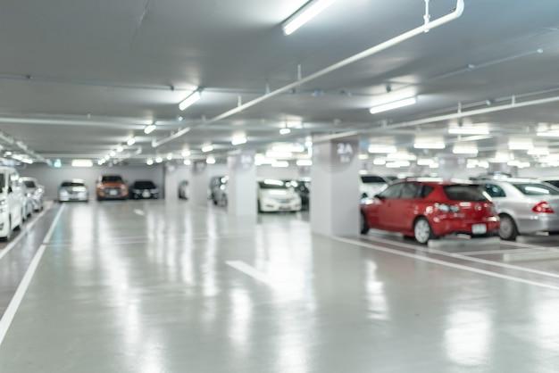 デパートやショッピングモール、背景の工業ビルの駐車場のインテリアにある多くの車の抽象的なぼかし画像