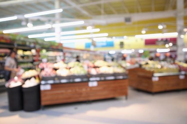 슈퍼마켓 매장의 식료품 선반에 있는 유기농 신선한 과일과 야채는 추상적으로 흐릿한 보케의 밝은 배경을 흐리게 합니다.
