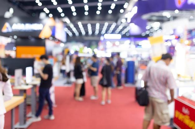Абстрактная нерезкость людей в выставочном зале события выставки экспо. деловая выставка, ярмарка вакансий или фондовый рынок. организация или корпоративное мероприятие, коммерческая торговля