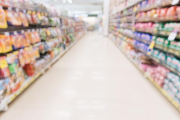 抽象ぼかしスーパーマーケットのディスカウントストアの通路と製品の棚のインテリアの焦点がぼけた背景