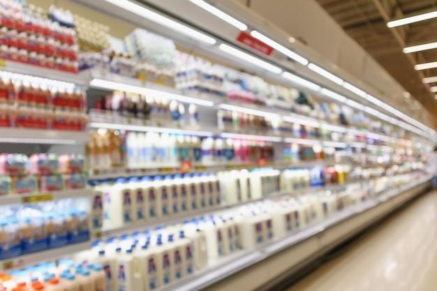 Полки холодильника продуктового магазина супермаркета абстрактного размытия с бутылками свежего молока и молочными продуктами