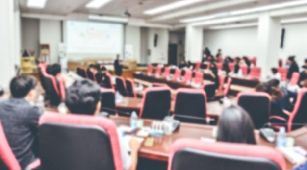 部屋で会議や会議をぼやけている抽象的な人々。