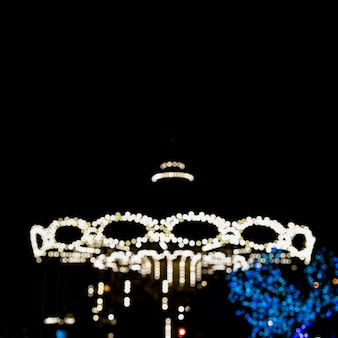 Abstract blurred background of vintage carousel at night