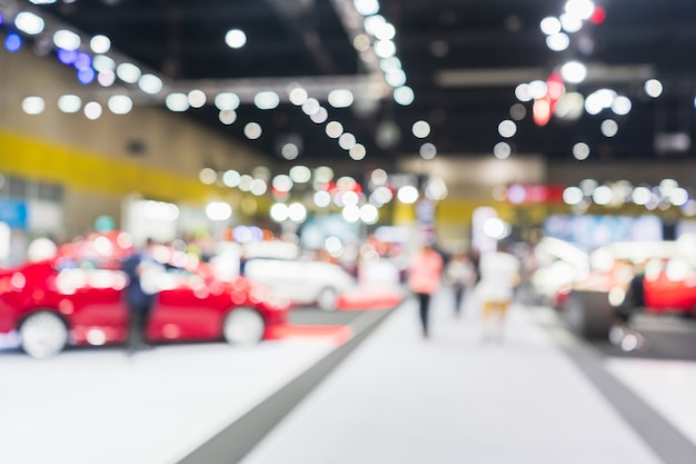 Abstract blurred image of cars exhibition show. blurred defocused image of public event exhibition hall showing cars and automobiles.