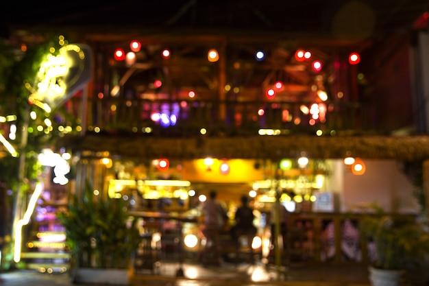 背景デザインの明るいボケ味と夜のストリートカフェの抽象的なぼやけた画像。
