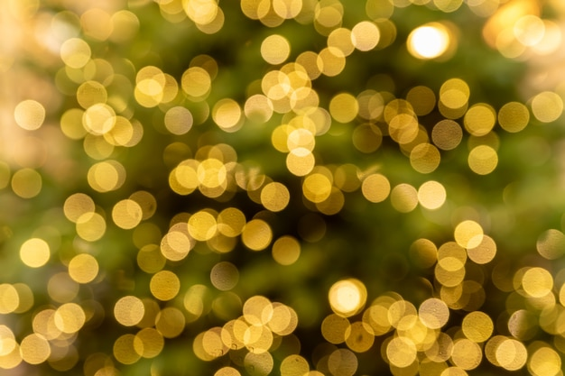 Абстрактные размытые огни на фоне в золотых тонах. - концепция празднования рождества.