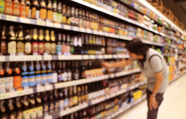 Abstract blurred of a man selecting beer bottles from the grocery shelf
