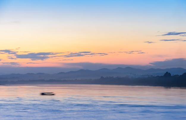 日没時の抽象的なぼやけた自然海と山の風景