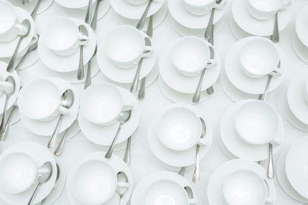 背景のコーヒーやティーカップの多くの白い列の抽象的なぼやけ。