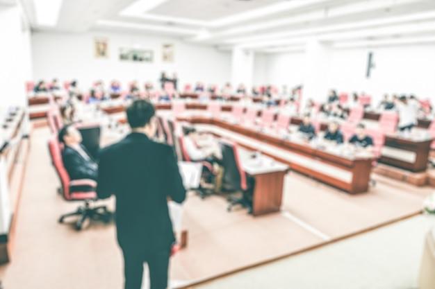 部屋で会議や会議のステージの人々に抽象的なぼやけたスピーカー。
