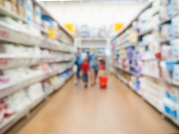 Abstract blurred supermarket aisle with unrecognizable customers as background Premium Photo