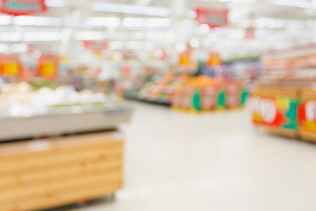 Abstract blurred supermarket interior with fresh fruits and vegetable on shelves and bokeh background