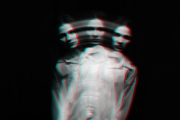 Abstract blurry female portrait of a psychotic with bipolar and schizophrenic disorders with red illumination on a black background. black and white with 3d glitch virtual reality effect