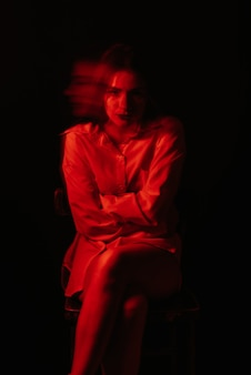 Abstract blurry female portrait of a psychotic with bipolar and schizophrenic disorders with red illumination on a black background
