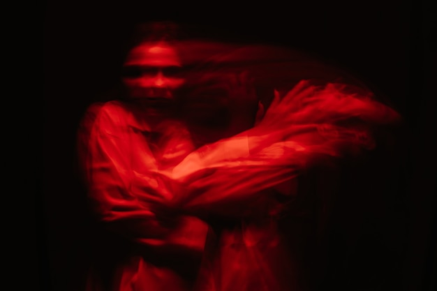 Abstract blurry portrait of a psychotic woman with mental disorders and bipolar disease in a white straitjacket