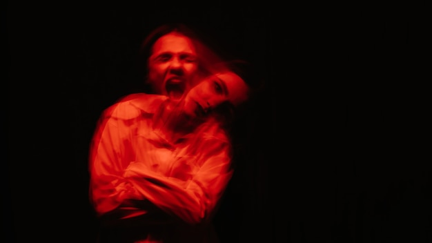Abstract blurry portrait of a psychotic woman with mental disorders with red lights on black background