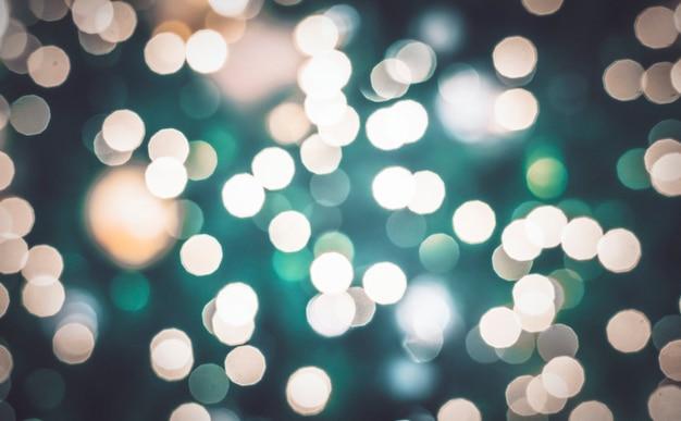 濃い緑色の背景にぼやけたボケライトと抽象的なボケライト。クリスマスと年末年始の背景