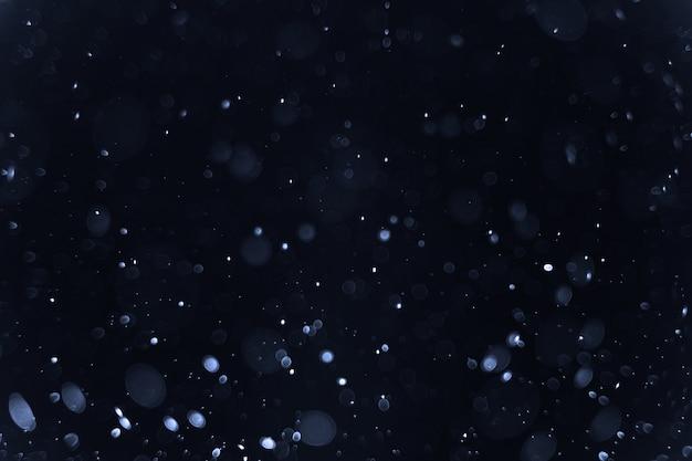 Абстрактный bokeh света на черном фоне, рождество и новый год концепции
