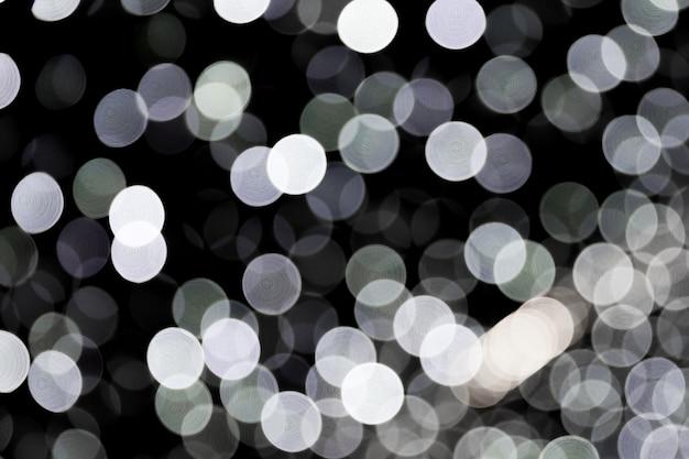 黒い背景に白い街の明かりの抽象的なボケ味