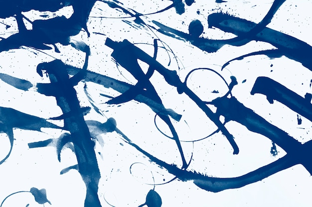 Abstract brush strokes and splashes of paint on paper. classic blue toning trend