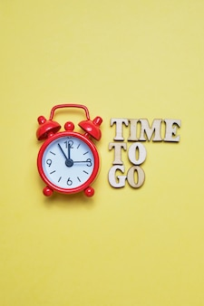 An abstract call to action - time to go. wooden letters next to the red clock