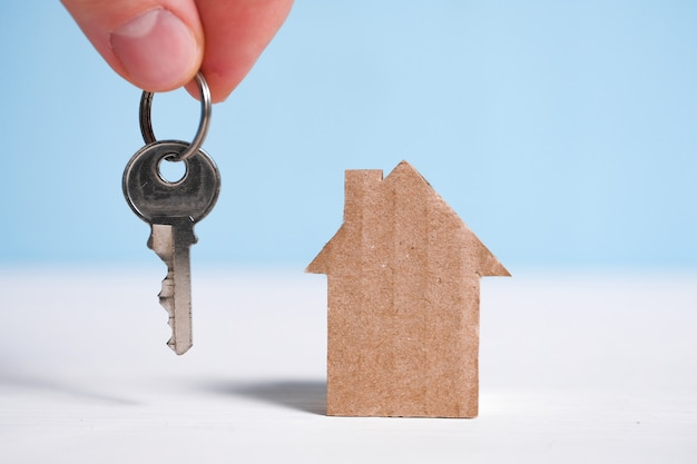 Abstract cardboard house next to a hand holding a house key.  buying a new home.