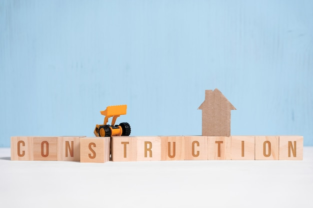 Abstract cardboard house next to wooden cubes with inscriptions and construction equipment.